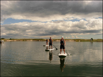 Three people doing stand up and paddle on Cape Cod water.