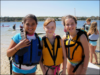 Three girls enjoying stand up and paddle fun at Paddle for the Bays event